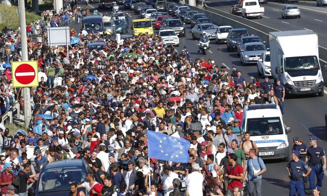Migrants march along the highway towards the border with Austria